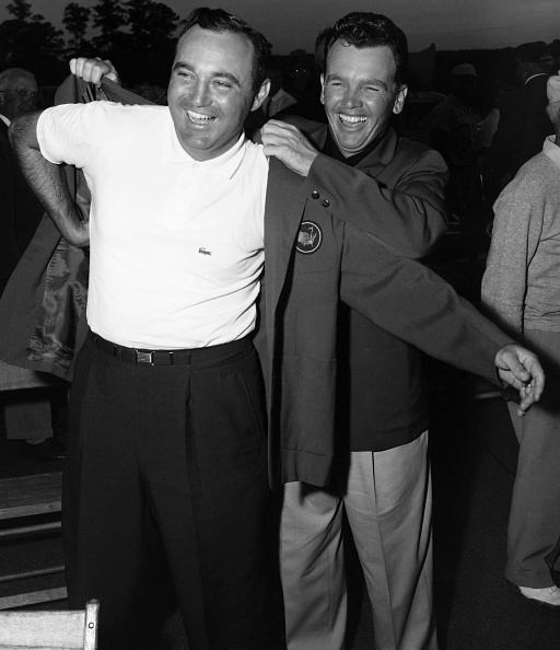 (Original Caption) Obviously enjoying the whole thing, Doug Ford (left) tries on the traditional green coat, symbol of triumph in the Masters Golf Tournament, with the aid of 1956 winner Jack Burke, Jr., here April 7th. Ford fired a blazing 66 on the final round to win the tourney with a score of 283. Sammy Snead was second with a score of 286.